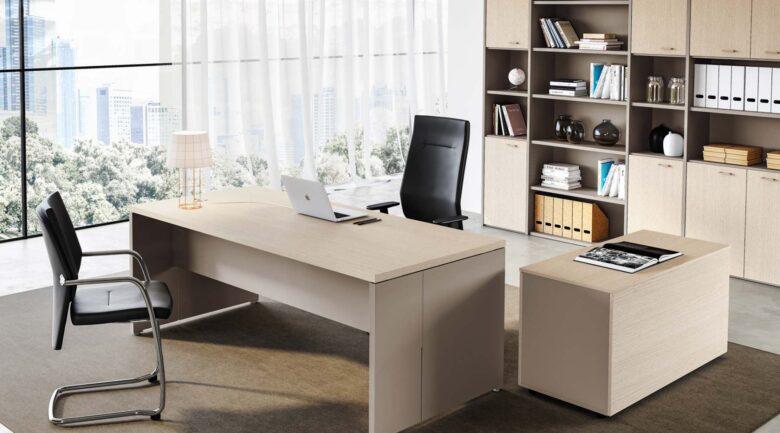 scrivania direzionale in legno chiaro delta evo con mobile e libreria e sedia in pelle nera e mac sulla scrivania