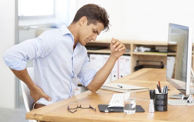 persona seduta alla scrivania con mal di schiena