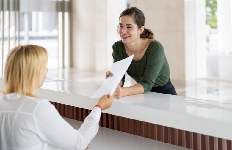 signorina al desk di una reception che porge un foglio a una signora