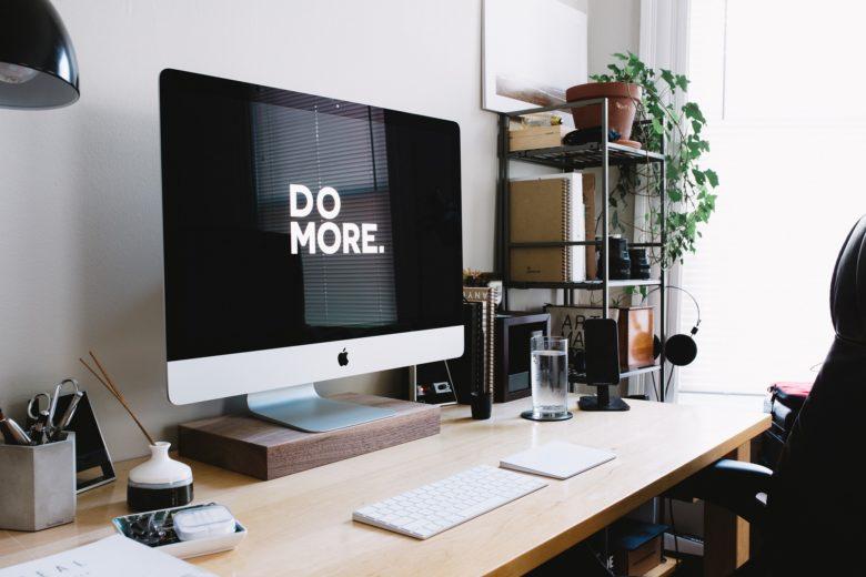 scrivania con pc mac e scaffale