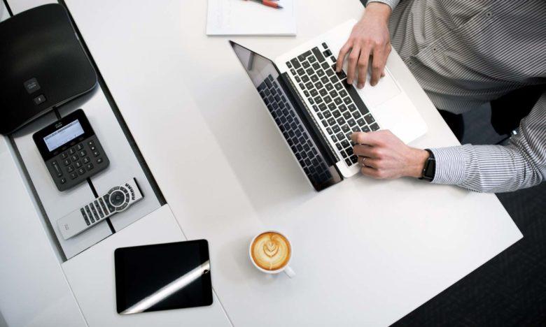 ragazzo lavora al mac su una scrivania con un cappuccino