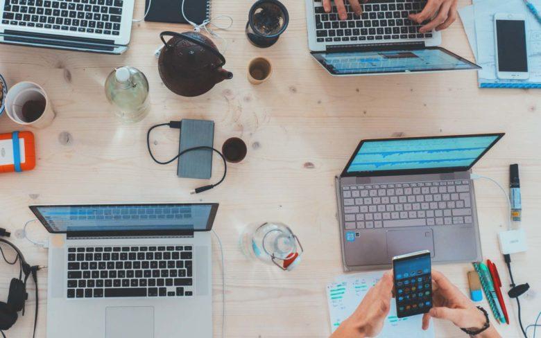 scrivania con 4 mac di persone che lavorano in gruppo in ufficio