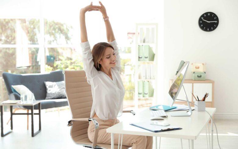 ragazza in ufficio seduta alla scrivania fa stretching da ufficio