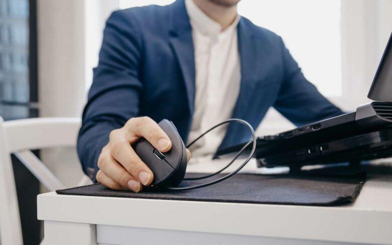 ragazzo alla scrivania usa mouse nero ergonomico