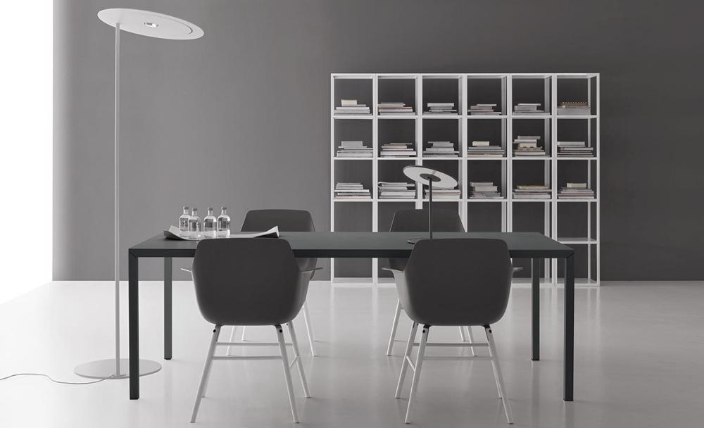 ufficio stile industriale con scrivania in metallo, poltroncine nere, libreria a muro in metallo bianco