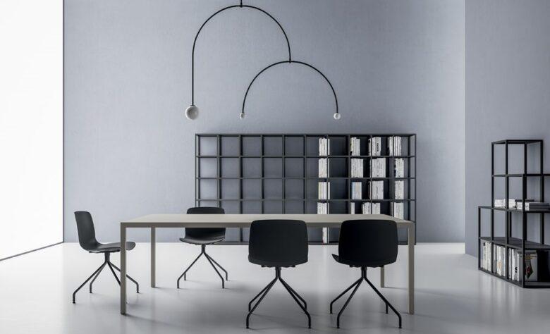 ufficio stile industriale con scrivania in metallo, poltroncine nere, libreria a muro in metallo